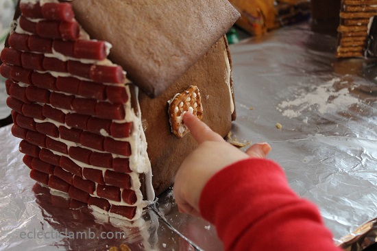 Little hand attaching Gingerbread house window