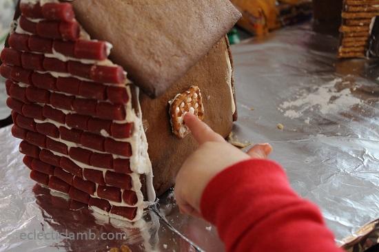 Little hand attaching Gingerbread house window
