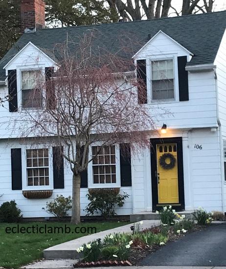 White house yellow door pink tree